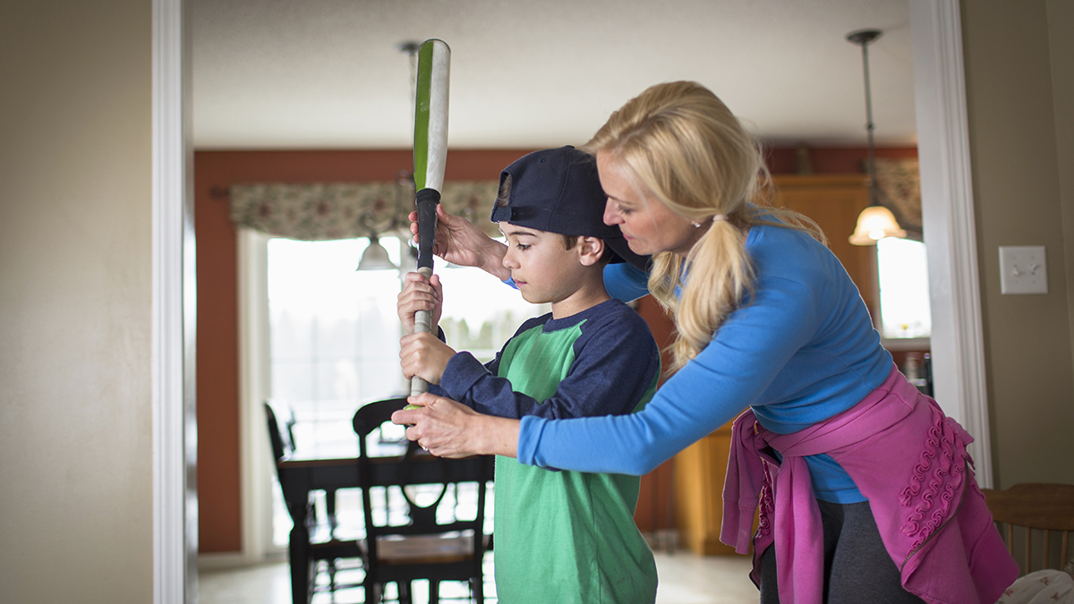 Mother teaching child to play baseball
