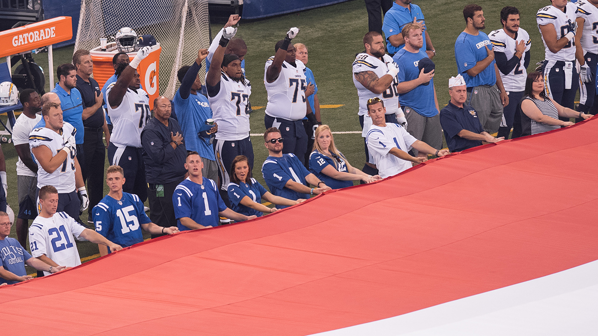 San Diego Chargers players raise their fist during the national anthem