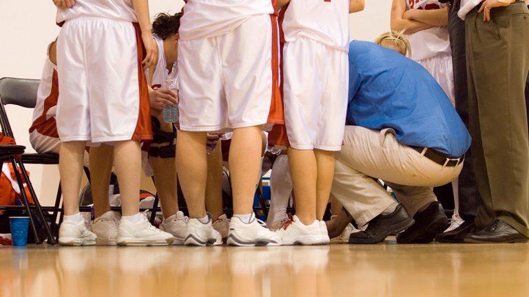 Girl basketball players huddle around coach squatting down instructing team