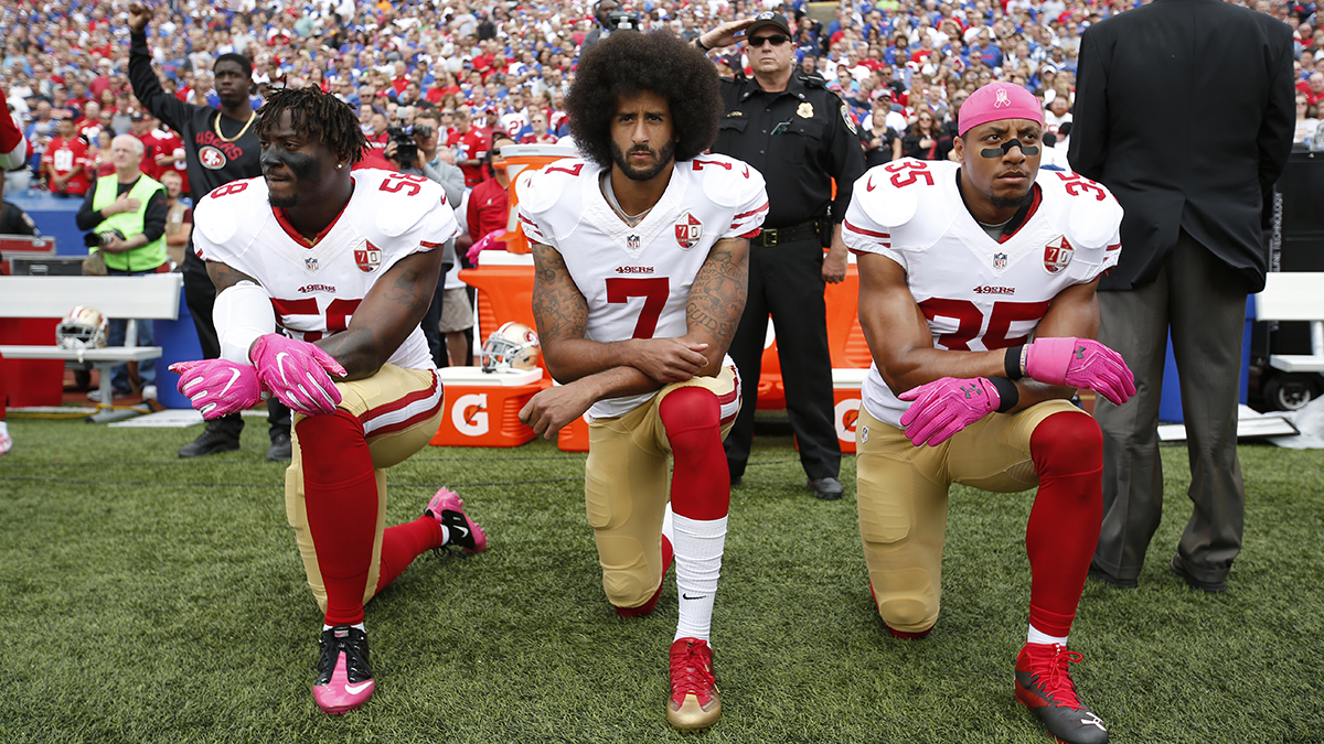 Colin Kaepernick and teammates Eli Herald and Eric Reid kneeling during the national anthem