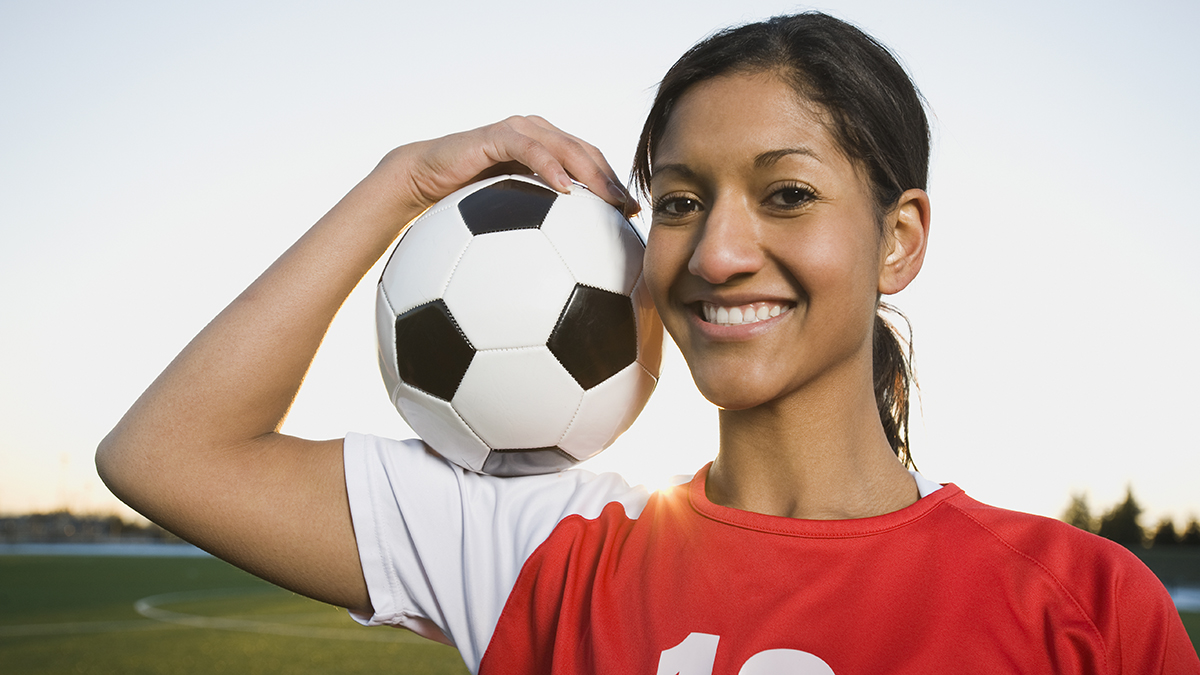 Girl holding up a soccer ball