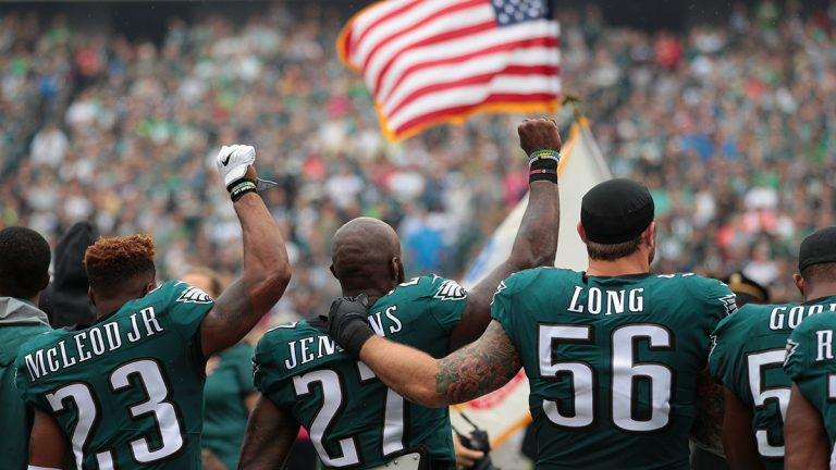 Rodney McLeod and Malcolm Jenkins raise their fists in protest while Chris Long of the Philidelphia Eagles puts arms around teammates in support