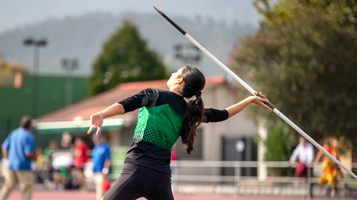 Girl with ponytail winds up to throw javelin on track