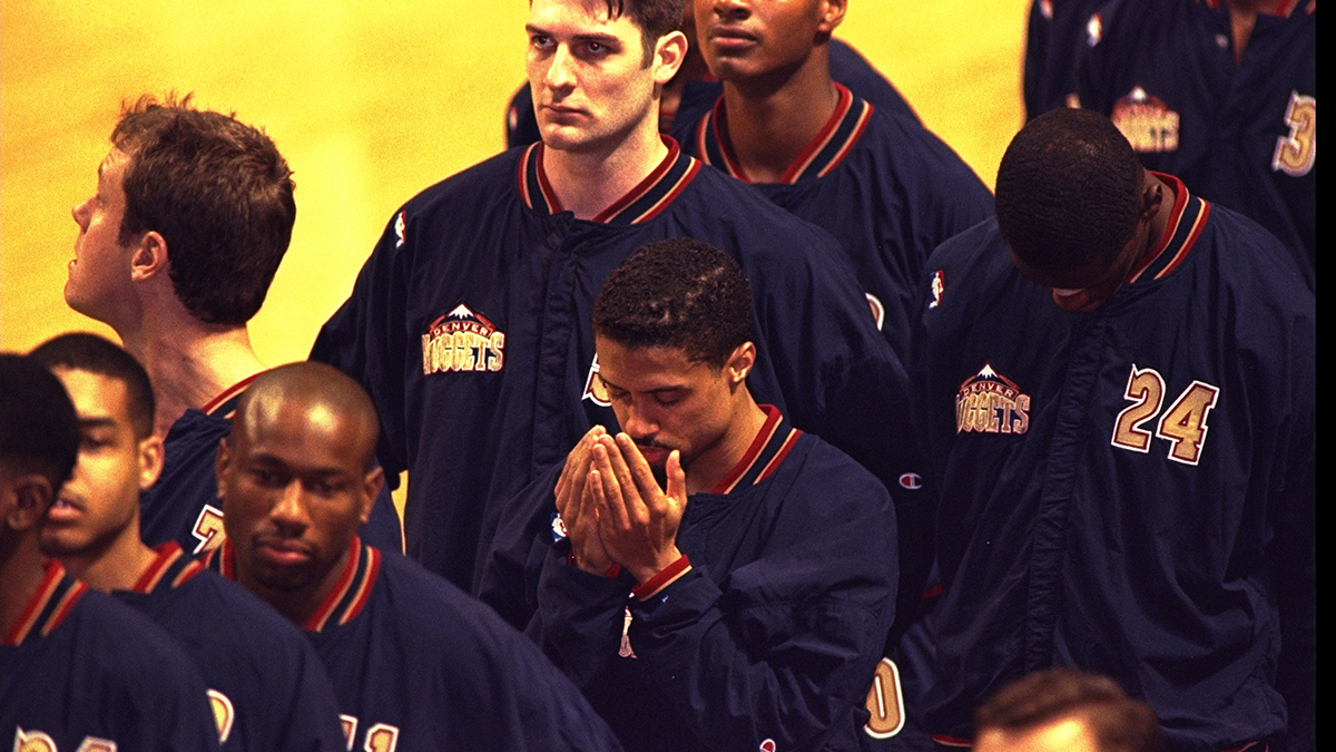 Point guard Mahmoud Abdul Rauf of the Denver Nuggets prays during the singing of the national anthem during a 1996 Nuggets game