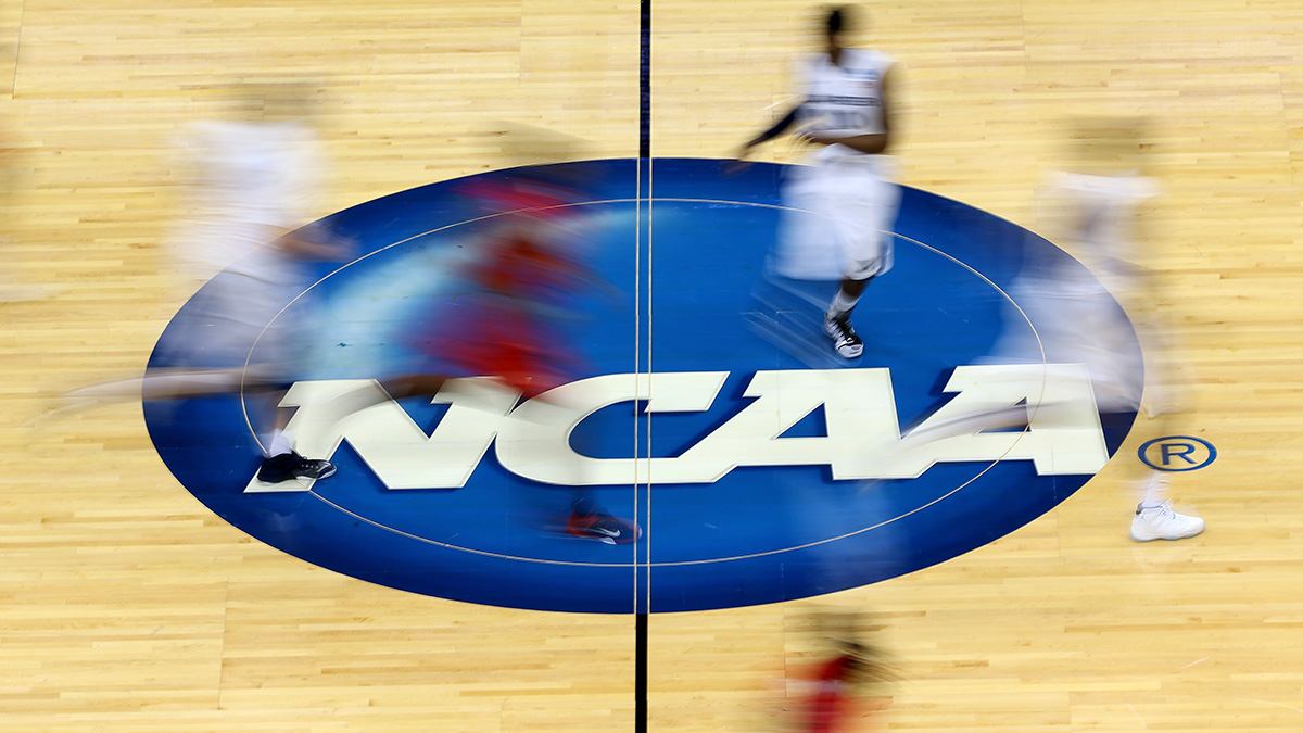 Basketball court with NCAA logo on it and basketball players running by