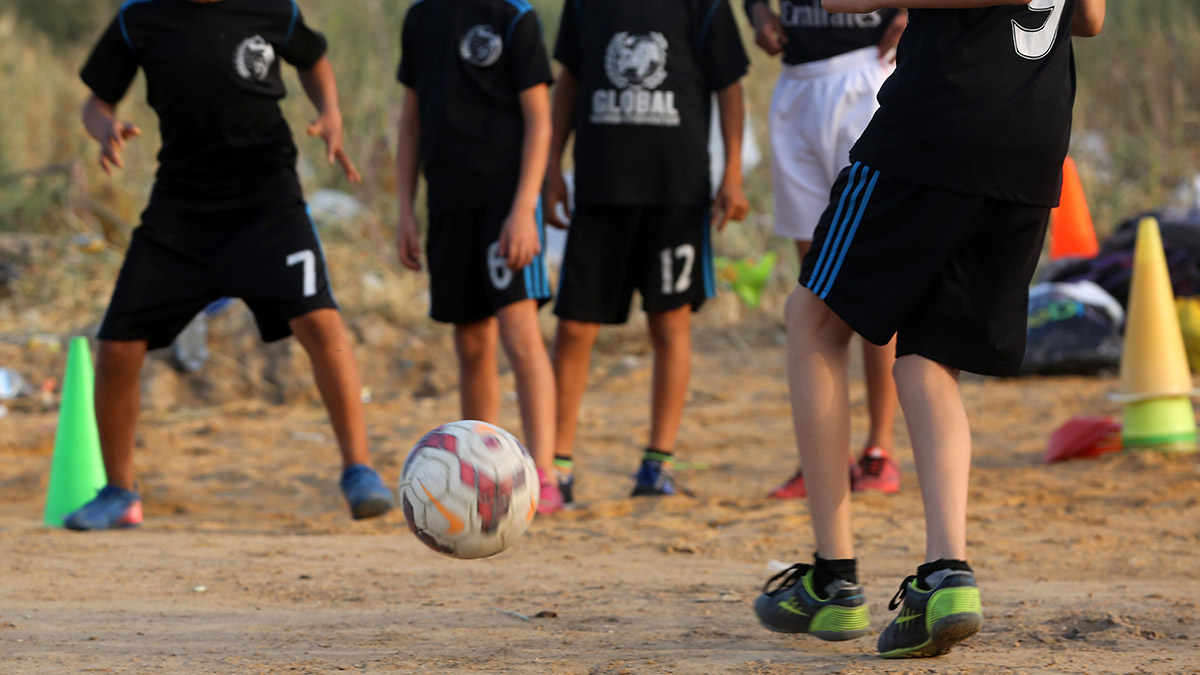 Children playing soccer in black uniforms for Soccer Without Borders