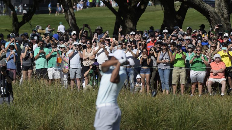 Fans take pictures as Tiger Woods hits his tee shot at hole No. 18 during the third round of the Arnold Palmer Invitational
