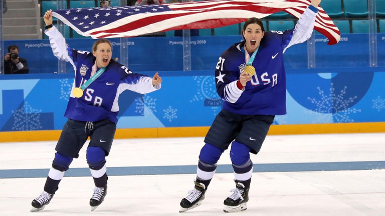Kendall Coyne and Hilary Knight of the U.S. women's hockey team skating on ice rink with gold medals