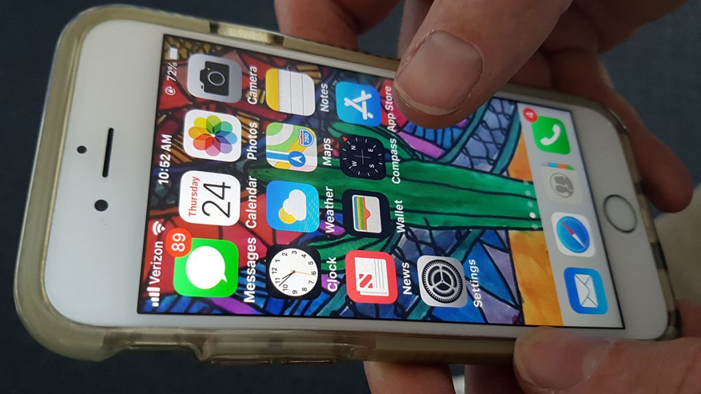 An unlocked iPhone showing home screen apps with someone's finger hovering over the app store