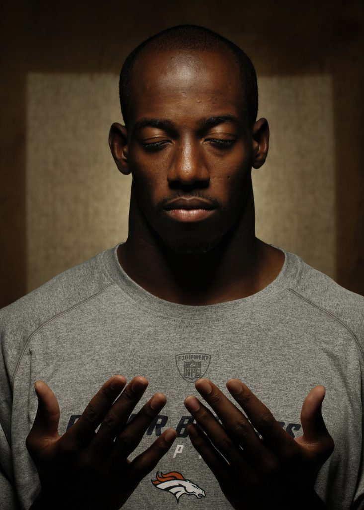 Former NFL player Hamza Abdullah holds up his hands and looks at his palms