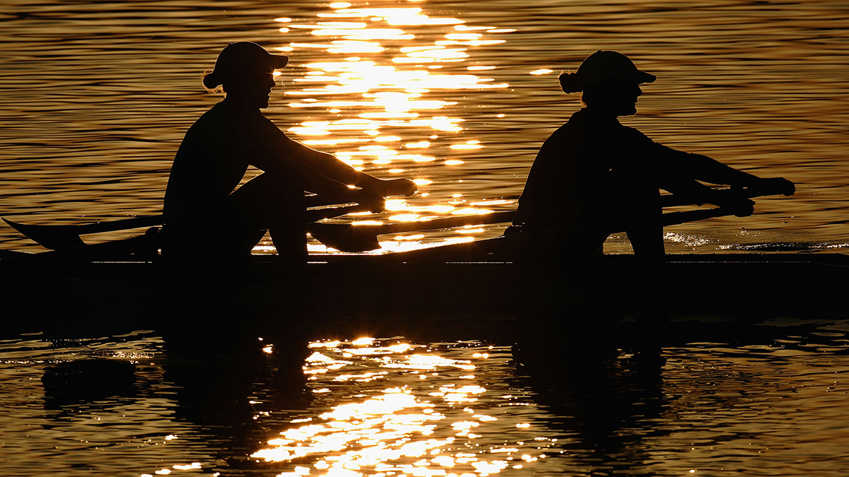 Kate Mackenzie and one other person rowing boat during sunset