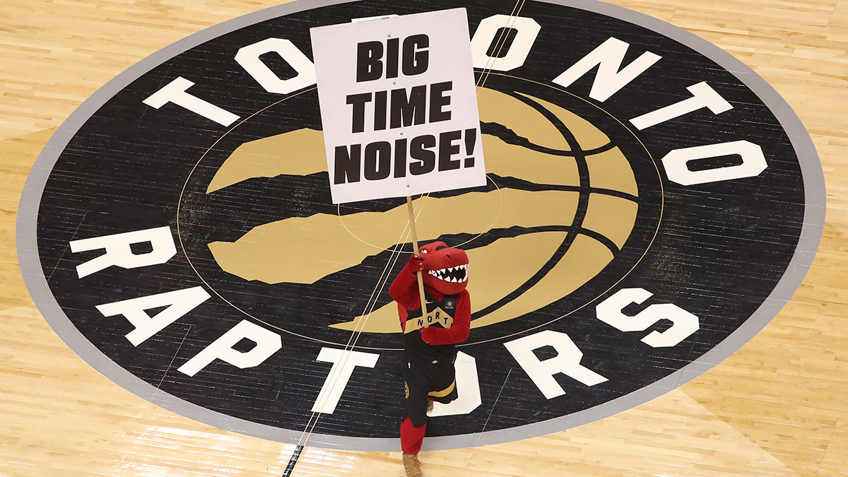 Raptor the mascot of the Toronto Raptors holds a sign at center court imploring fans to make noise over the team logo.