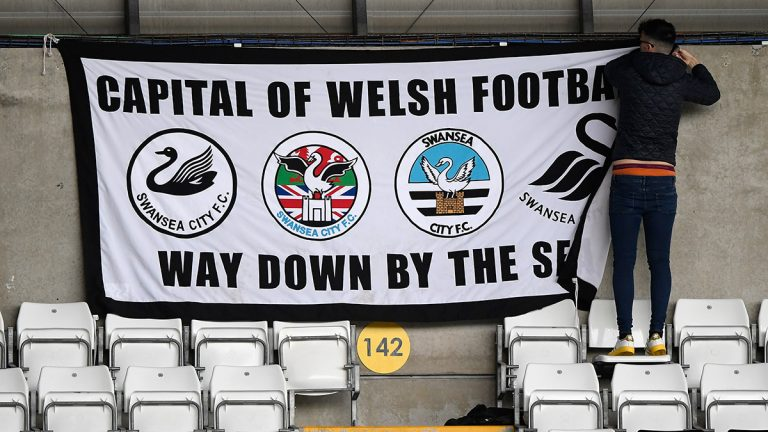 A supporter of Swansea City Football Club hangs up a flag before a match