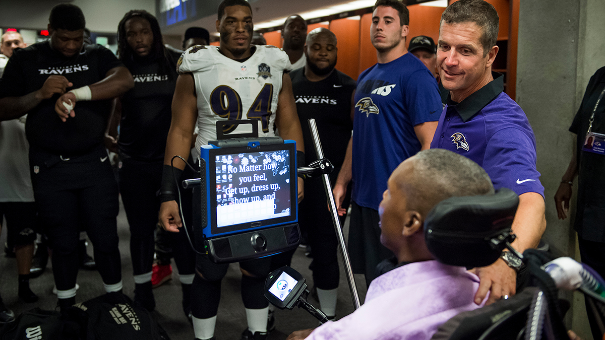 Former NFL player O.J. Brigance speaking to Baltimore Ravens coach John Harbaugh and players in locker room