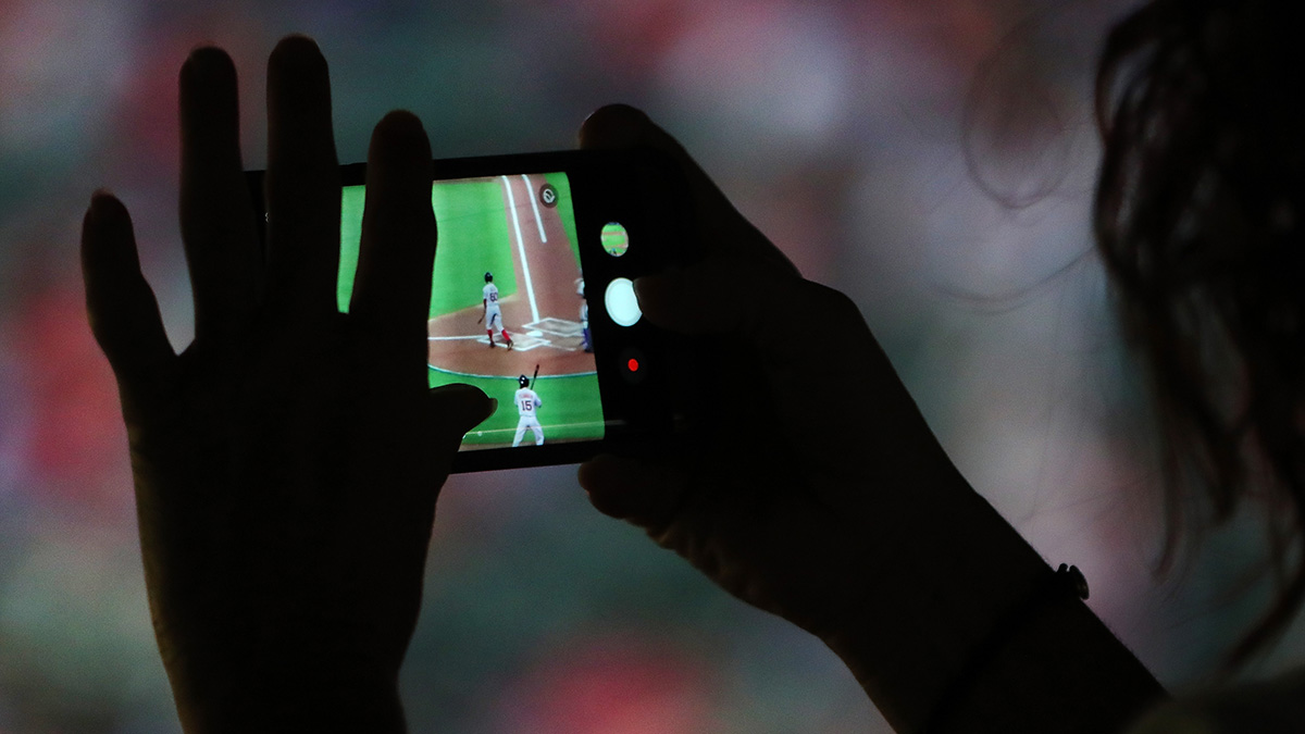 Fan taking a photo on phone during a 2017 baseball game