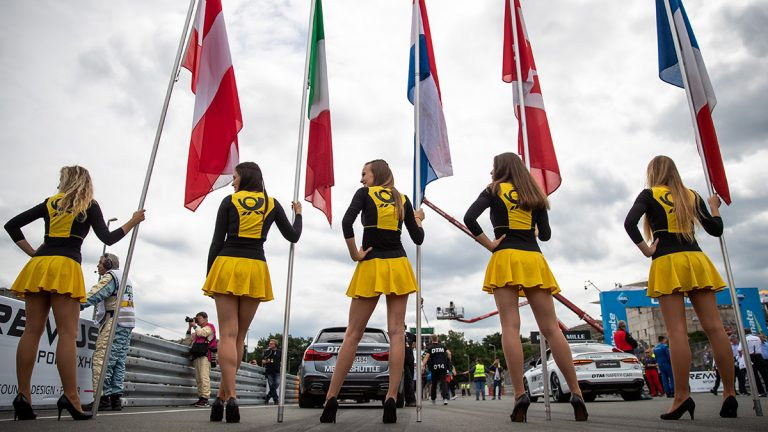 Five girls in short black and yellow dresses stand in a line holding flags from different countries at the start of a car race