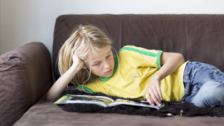 Child lays inactive while listening to music and reading a book
