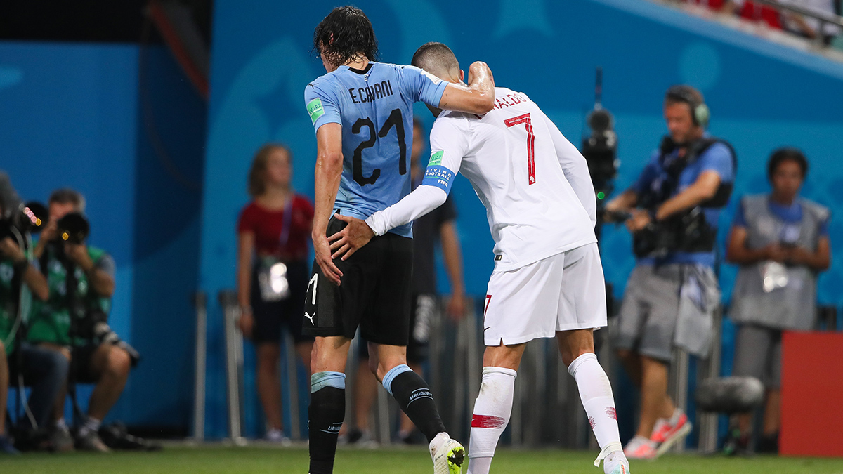 Christiano Ronaldo drapes injured Edison Cavani's arm over him to help Cavani off the field during World Cup soccer game