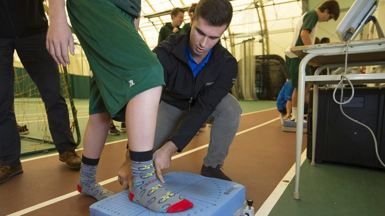 A student gets tested on their balance during a concussion test