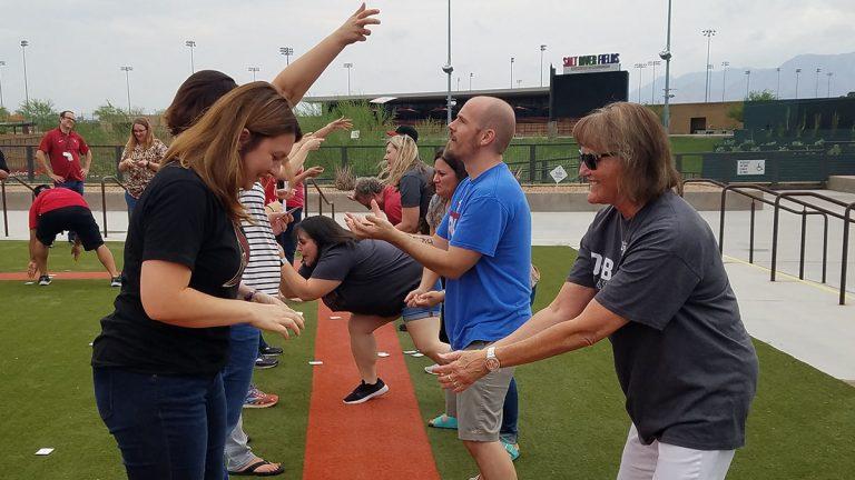 Adults playing tailgate games near Salt River Stadium