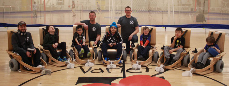 disabled youths play indoor adaptive floor hockey