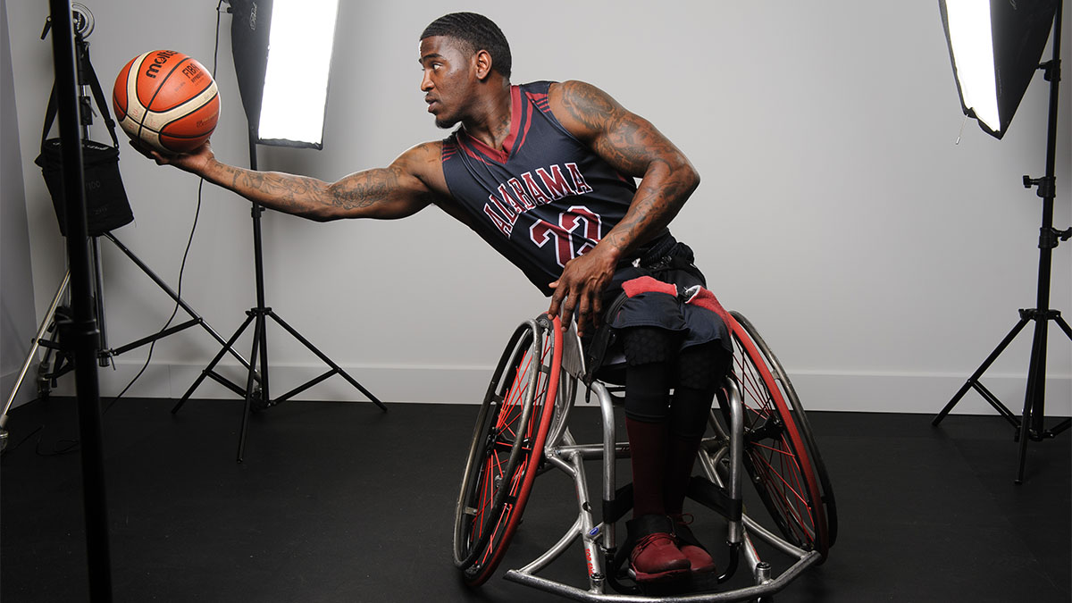 Dequel Robinson in University of Alabama basketball jersey sitting in wheelchair with outstretched arm holding basketball