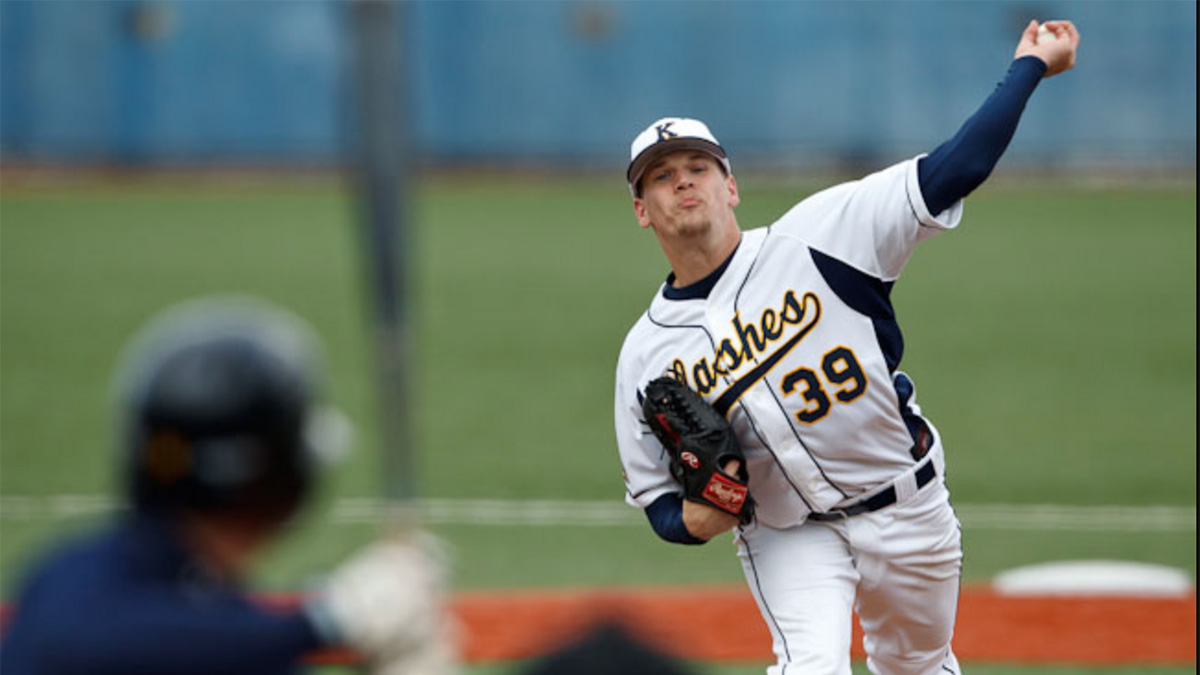 Kent State baseball player in white and navy uniform pitches baseball