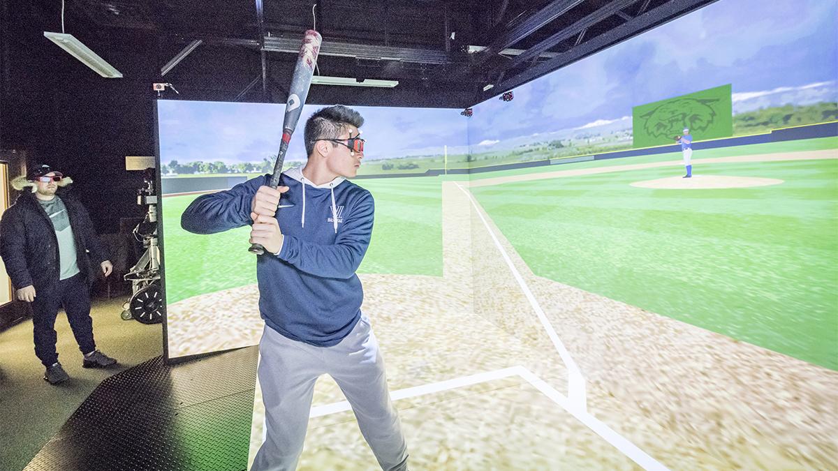 Boy in athletic clothes holding a baseball bat doing virtual reality baseball