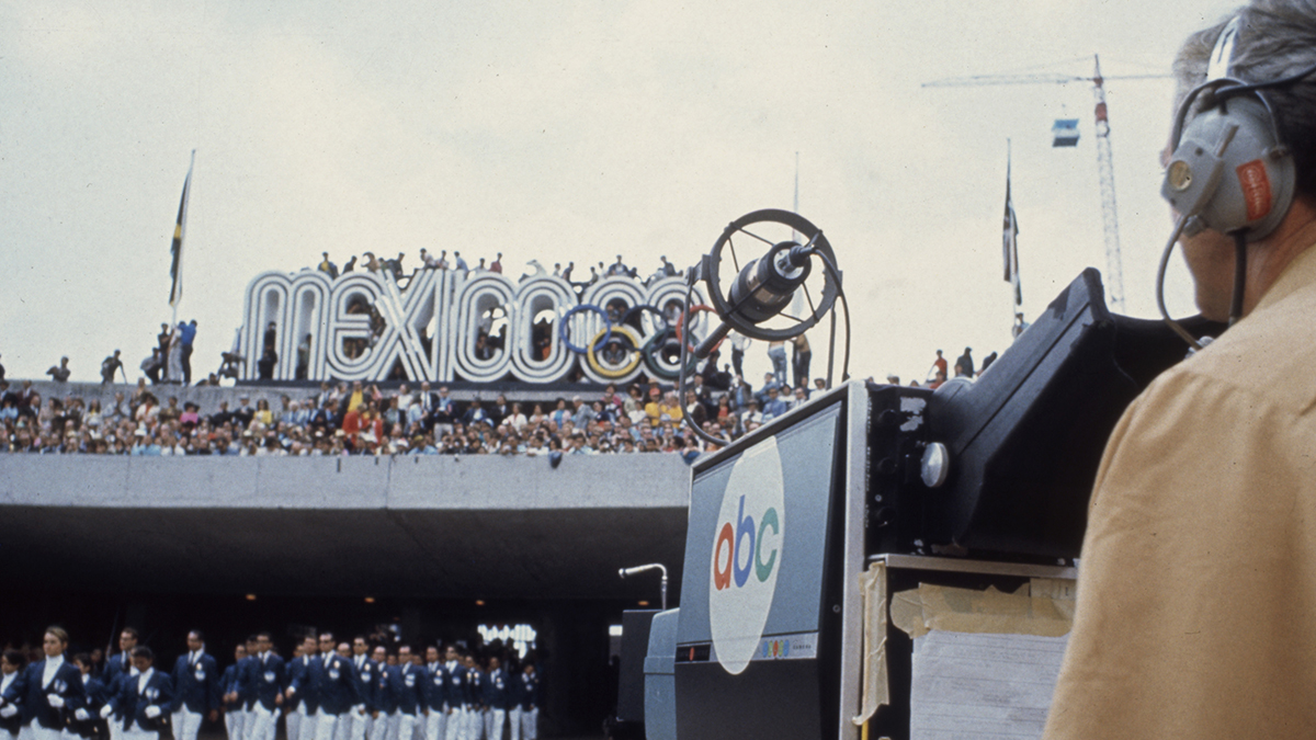An ABC newscaster records athletes entering the stadium at the 1968 Olympics