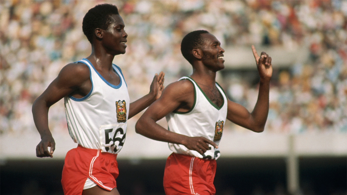 Kip Keino, from Kenya, runs alongside his teammate after winning a gold medal at the 1968 Summer Olympics
