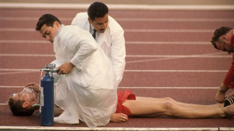 A runner on the track is given oxygen after collapsing during race