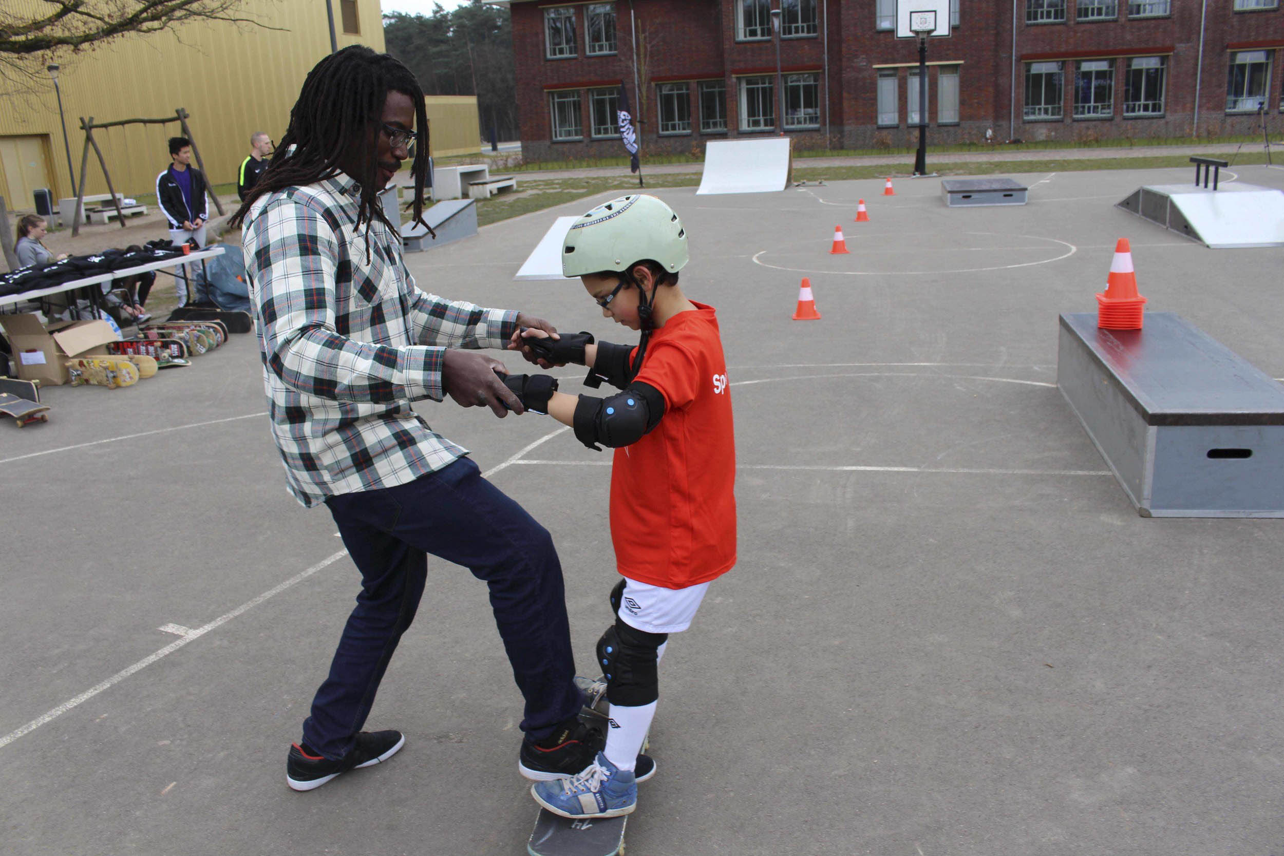 Neftalie Williams helps young skateboarder