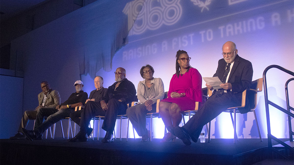 Kenneth Shropshire, John Carlos, Lance Wyman, Harry Edwards, Wyomia Tyus, Gina Hemphill-Strachan, and Paul Hoffman discuss the athlete protests at the 1968 Summer Olympics