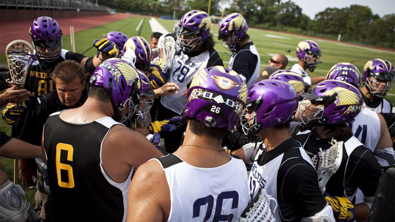 Lacrosse players with purple helmets in a huddle