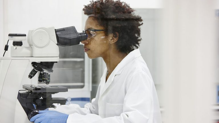 Female scientist looking through a microscope