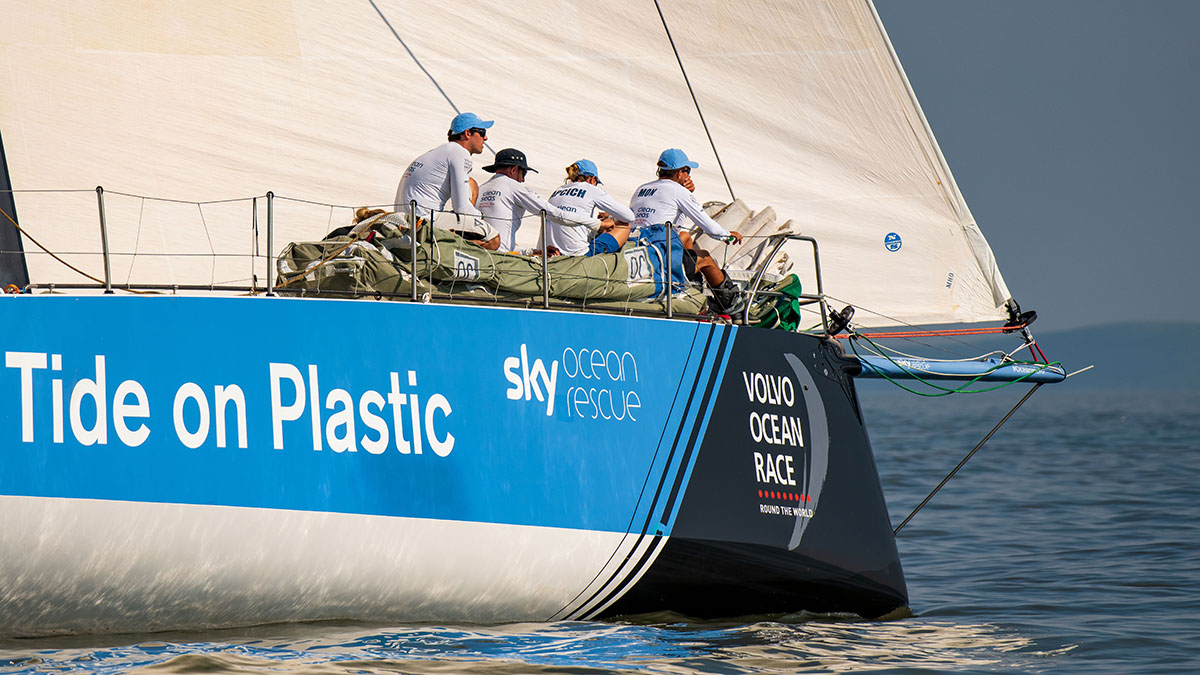 Sailors in sailboat race