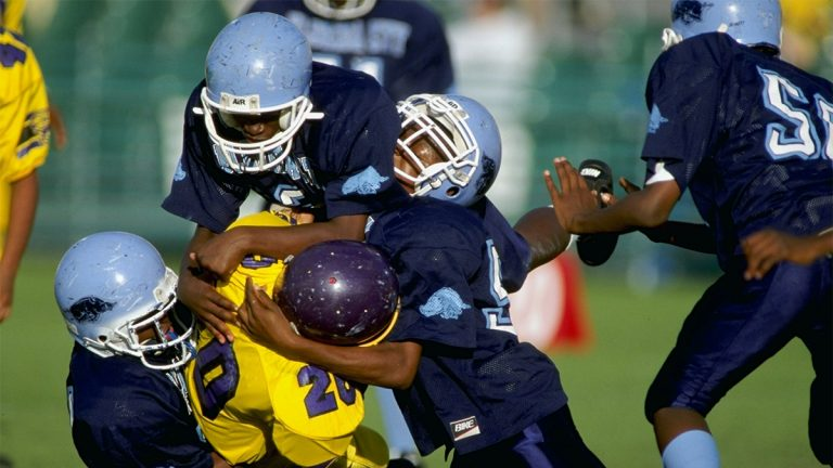 Five kids playing football and tackling
