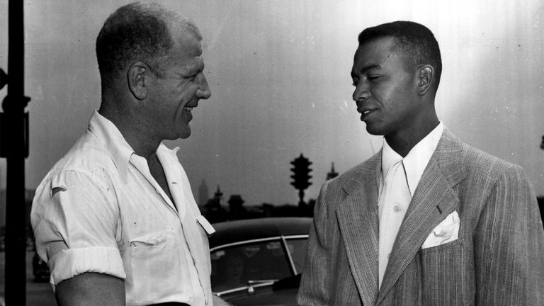 President Bill Veeck of the Cleveland Indians and the American league's first black player, Larry Doby smiling and speaking to each other.