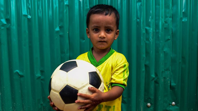 A child holding a soccer ball at a refugee camp.