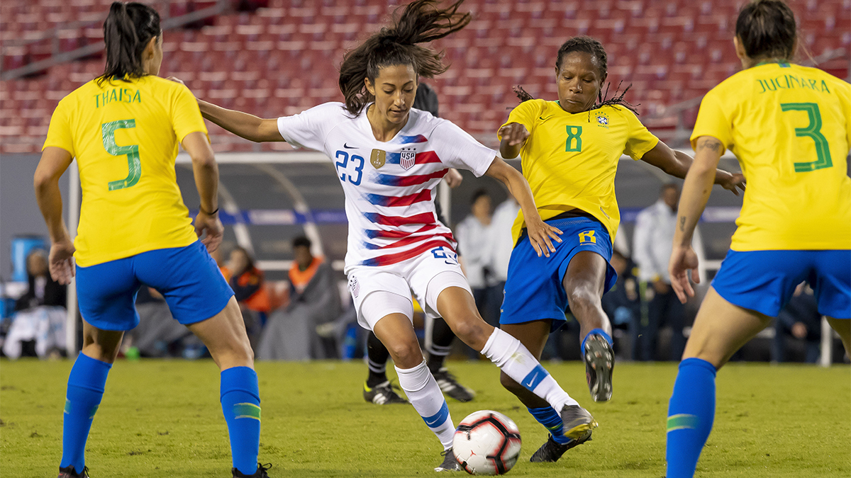 Christen Press of the U.S. dribbles ball through Brazil players in the She Believes Cup in 2019
