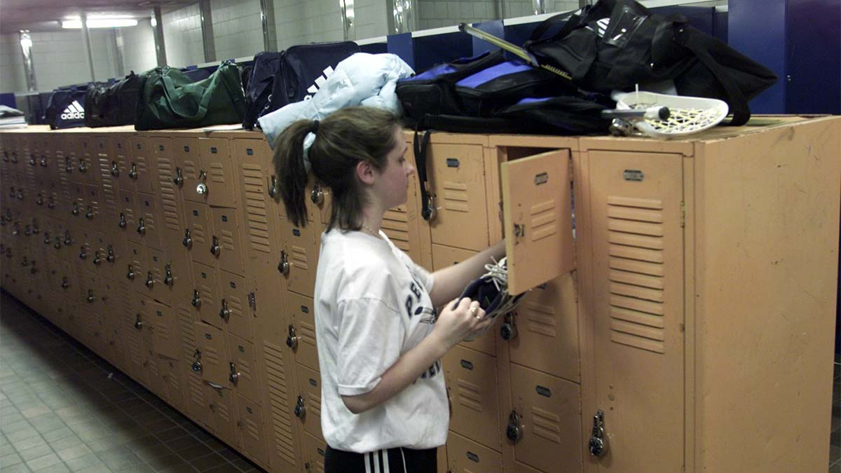 High school girl grabbing shoes from her locker in girls' locker room