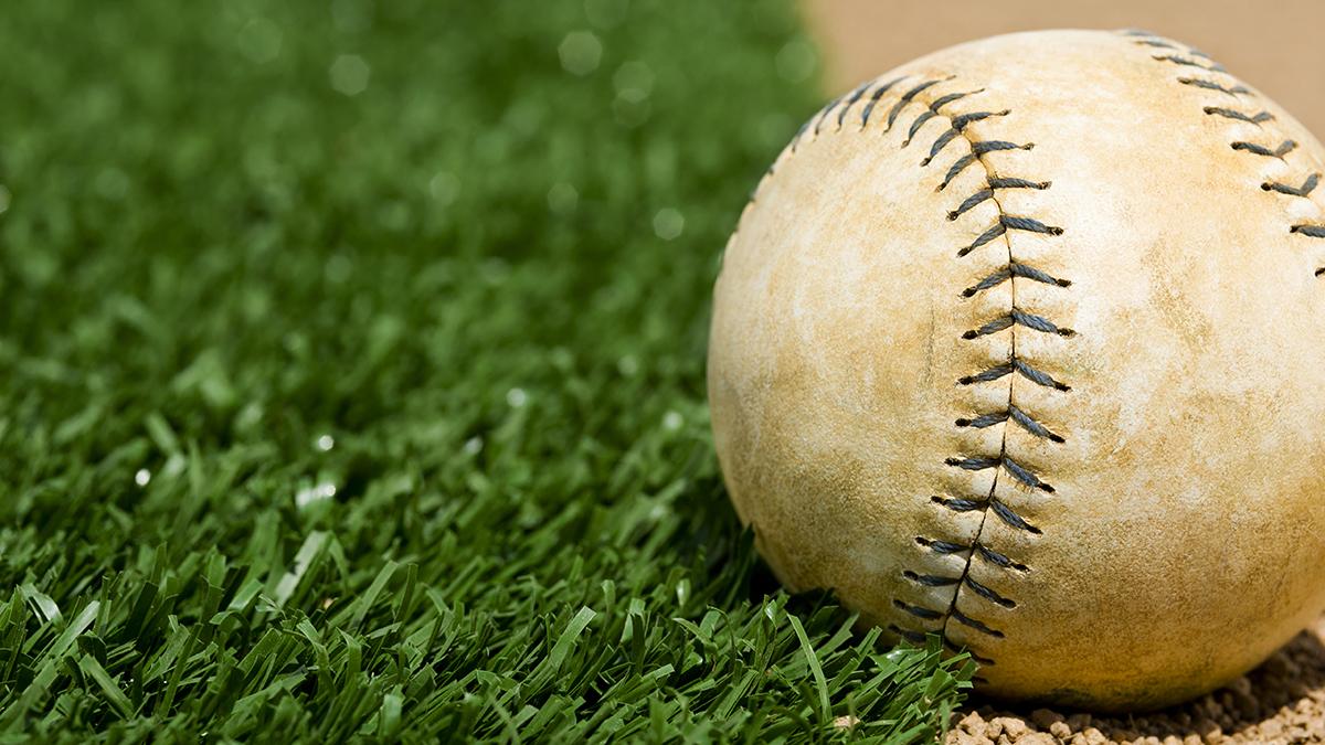 An Old Softball sitting between the infield grass and dirt of a softball diamond
