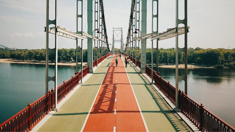 Pedestrians on a bridge over water that features a painted track through the middle of the pathway.