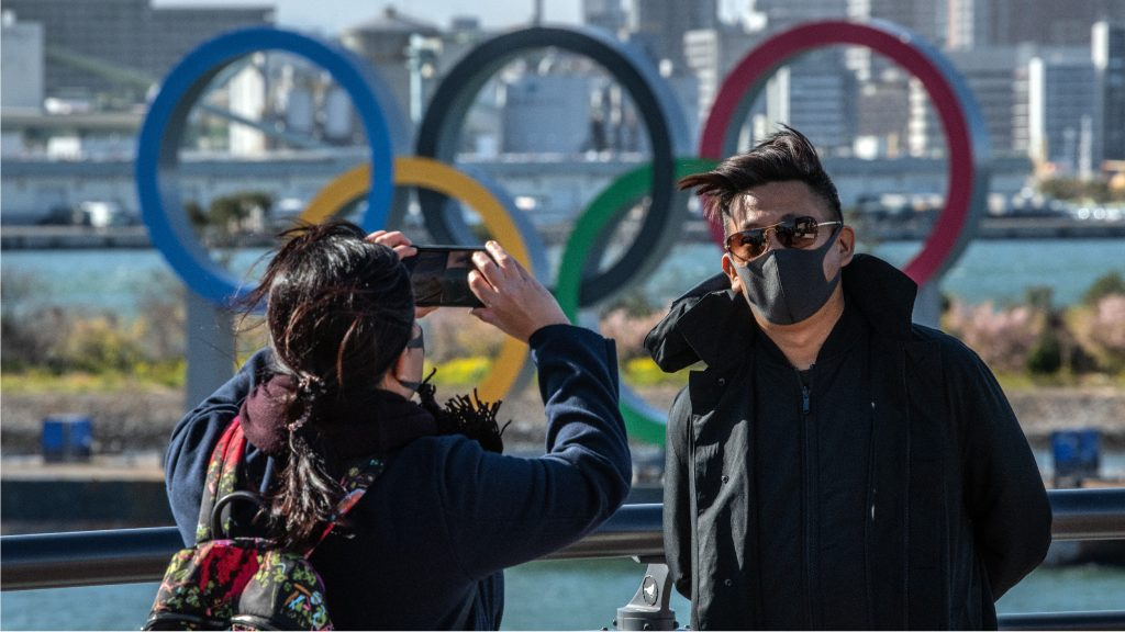 TOKYO, JAPAN - MARCH 05: A man wearing a face mask has his photograph taken in front of the Olympic Rings in Odaiba on March 5, 2020 in Tokyo, Japan. An increasing number of events and sporting fixtures are being cancelled or postponed around Japan while some businesses are closing or asking their employees or work from home as Covid-19 cases continue to grow and concerns mount over the possibility that the epidemic will force the postponement or even cancellation of the Tokyo Olympics. (Photo by Carl Court/Getty Images)