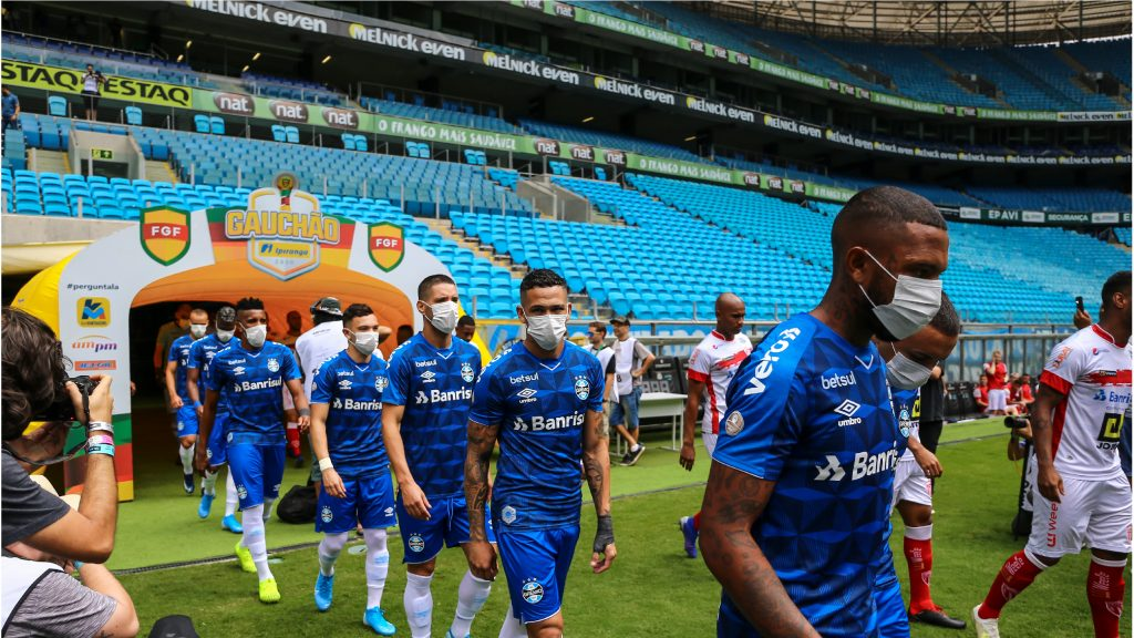 PORTO ALEGRE, BRAZIL - MARCH 15: Players of Gremio enter the field wearing masks before the match between Gremio and Sao Luiz as part of the Rio Grande do Sul State Championship 2020, to be played behind closed doors. (Photo by Lucas Uebel/Getty Images)