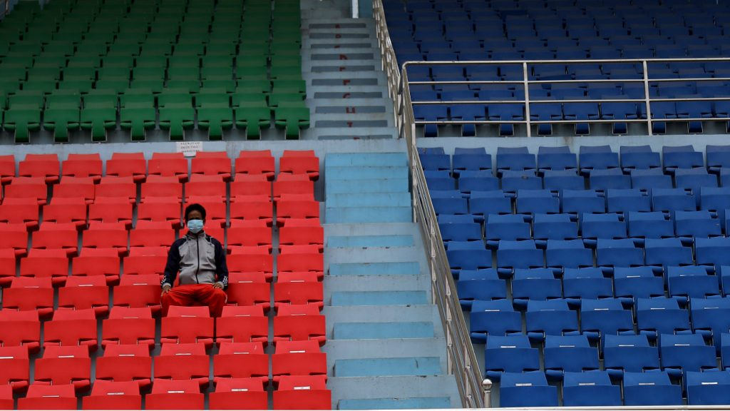 A man wearing a protective mask sitting in an empty stadium during the twenty-second day of lockdown in an effort to control the spread of COVID-19 in Kathmandu, Nepal, on April 14, 2020. (Photo by Saroj Baizu/NurPhoto via Getty Images)