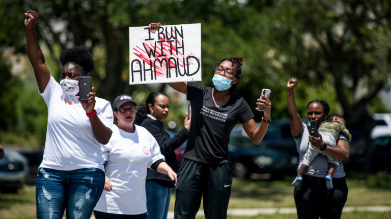 BRUNSWICK, GA - MAY 09: Demonstrators raise their fists at a parade of passing motorcyclists riding in honor of Ahmaud Arbery at Sidney Lanier Park on May 9, 2020 in Brunswick, Georgia. Arbery was shot and killed while jogging in the nearby Satilla Shores neighborhood on February 23. (Photo by Sean Rayford/Getty Images)
