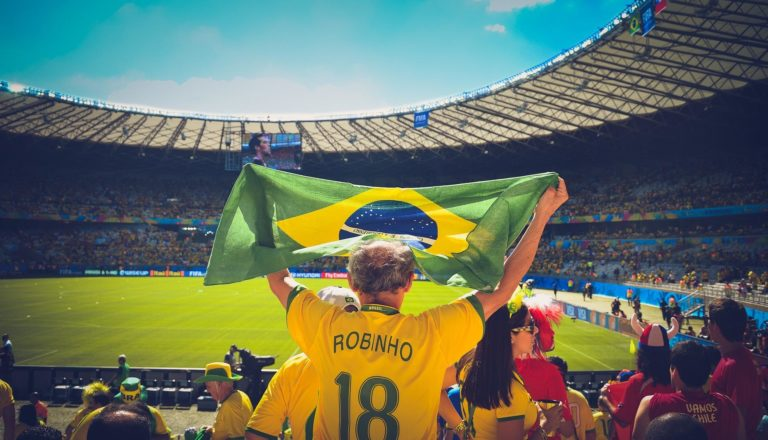 Man holding Brazilian flag at a soccer game