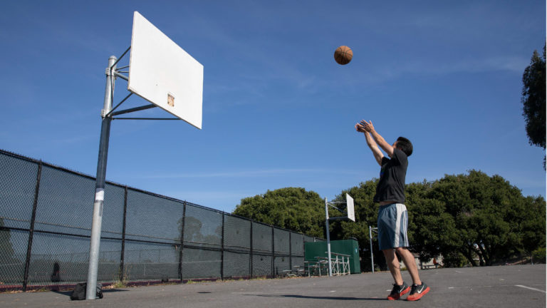 SAN FRANCISCO, CALIFORNIA - MAY 07: A man plays basketball after baskets are removed from basketball hoops at Mills High School on May 07, 2020 in San Francisco, California. The school removes baskets from basketball hoops to prevent people from gathering to play basketball. (Photo by Liu Guanguan/China News Service via Getty Images)