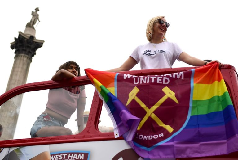 Pride supporters holding a LGBT pride flag on a bus in London.